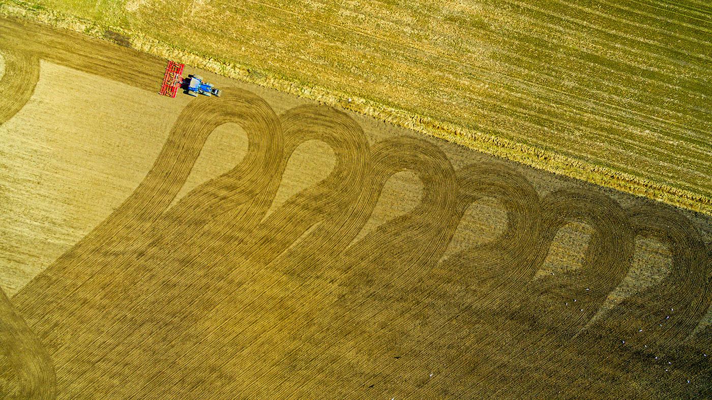 Luft foto af en traktor, der kører over en mark og danner et mønster