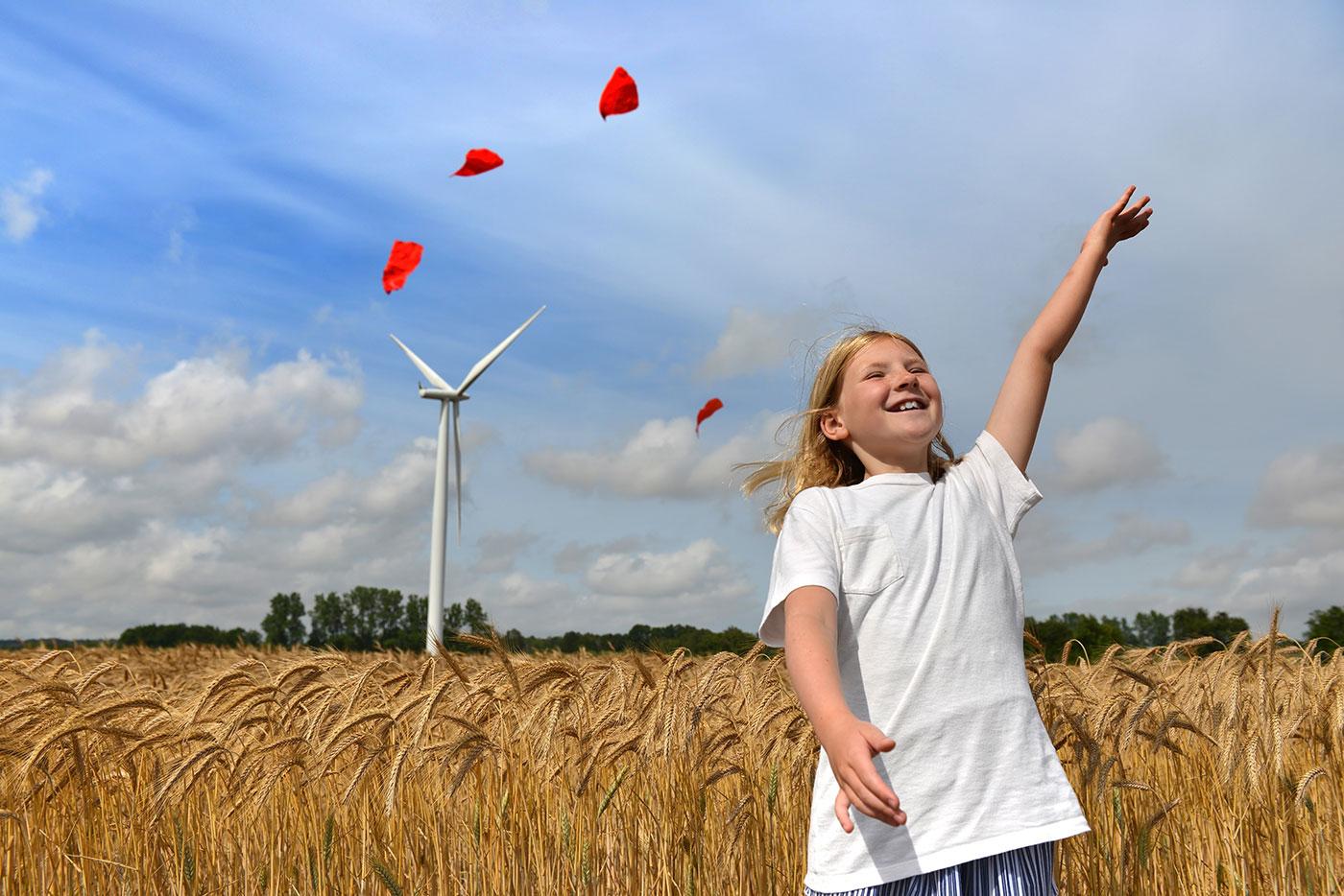 Foto af en pige, der løber og leger udendørs med vindmølle i baggrunden
