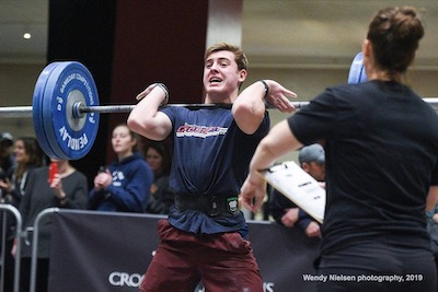 Our CrossFit trainer Michael competes and lifts a dumbbell.