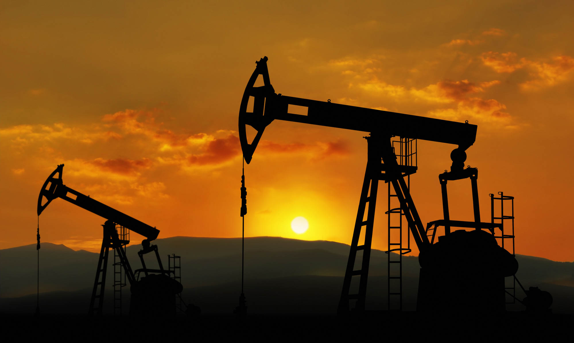 Background image of oil filed and pumps at sunset