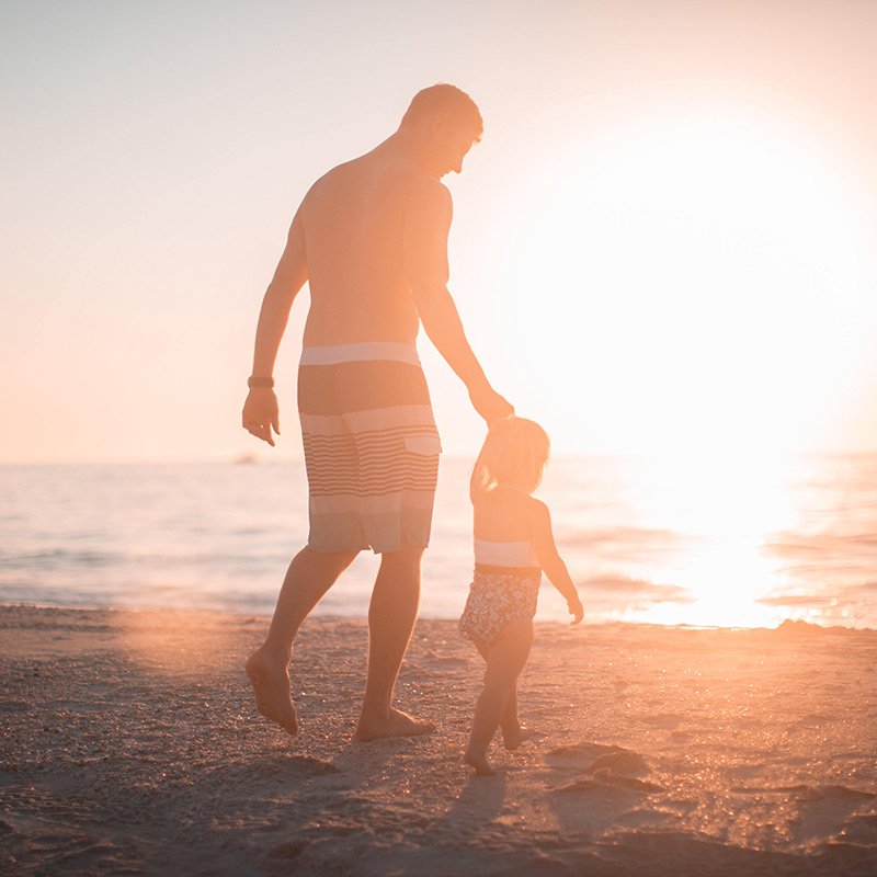 Mann og avkom på stranda mot solnedgang