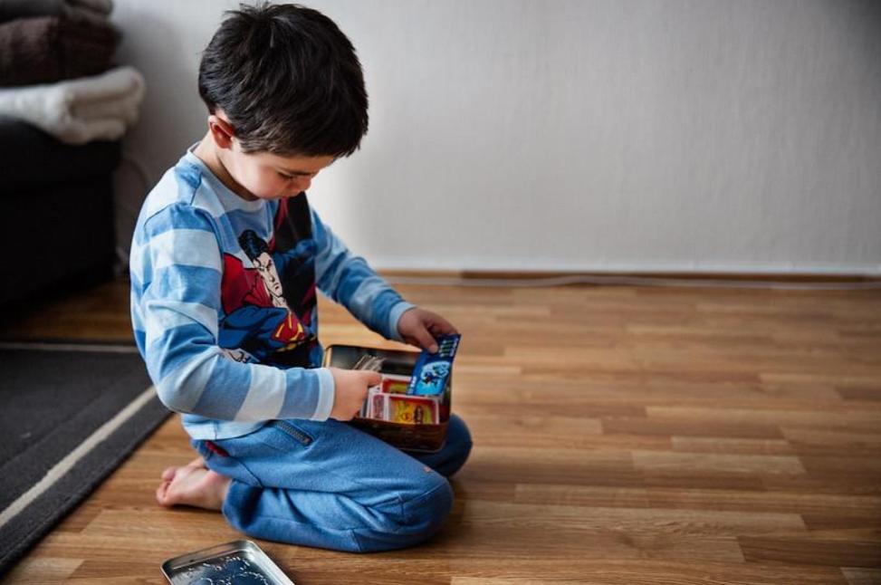 Foto: Lite barn sitter på gulvet og leker for seg selv