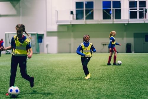 En ung jente med hijab ler og smiler mens hun spiller fotball med andre unge jenter