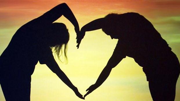 Foto: To mennesker står foran en solnedgang og legger armene sine sammen slik at de utgjør ett hjerte.