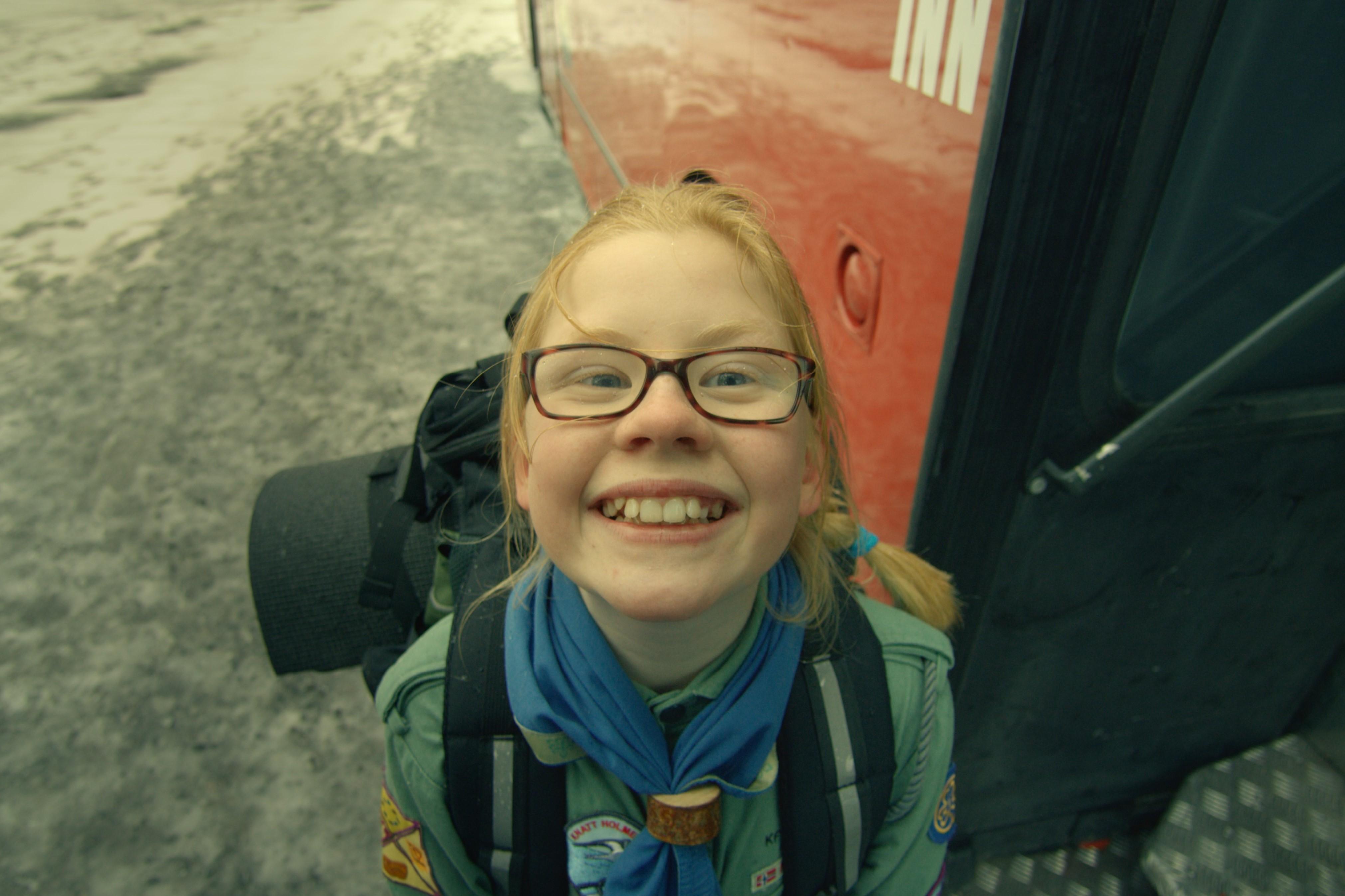 Speiderjente med briller smiler bredt opp i kamera
