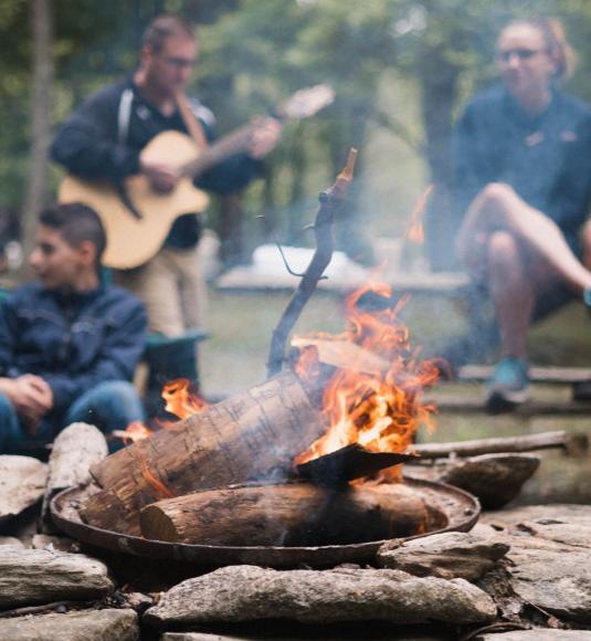 Foto: Et leirbål brenner i forgrunnen av voksne og unge som spiller gitar og prater.