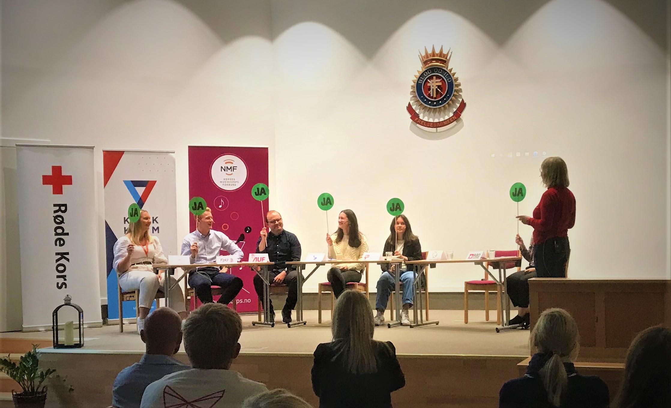 Foto: Ungdomspolitikere i paneldebatt holder grønne JA-plakater opp under Arendalsuka