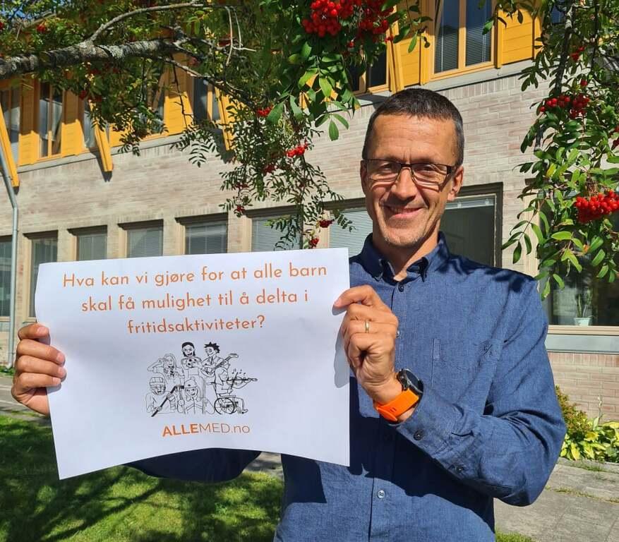 """Ordfører Jon Halvor Midtmageli smiler mot kamera i solen utenfor kommunehuset og holder opp en plakat som sier """"Hva kan vi gjøre for at alle barn skal få muligheten til å delta i fritidsaktiviteter?."""
