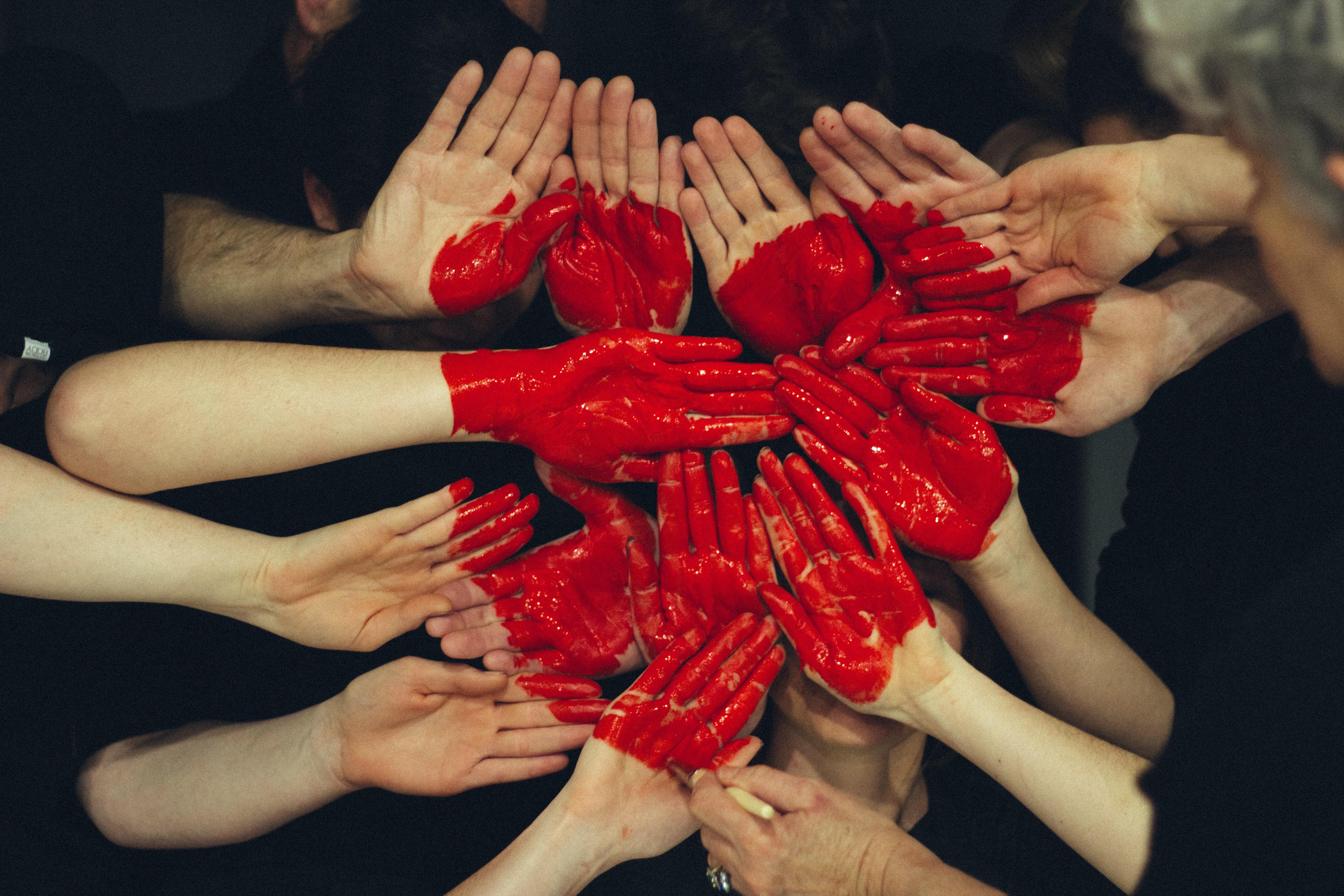Foto: Svartkledde mennesker med rødmalte hender samler hendene med håndflatene mot kamera. Hendene er malt ulikt i rødt og utgjør et hjerte når hendene samles.