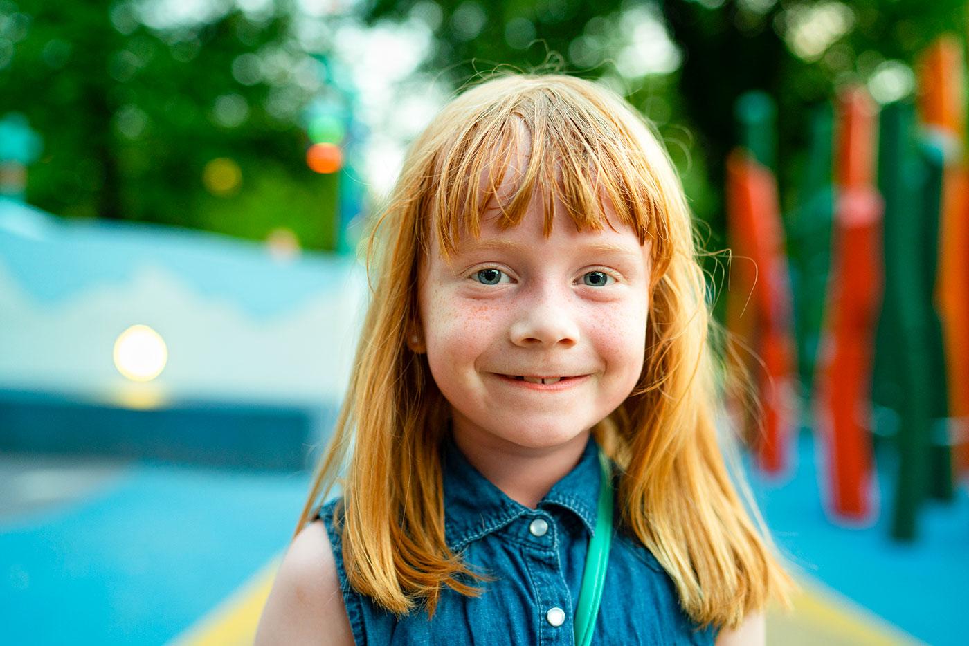 Foto af smilende rødhåret pige med fregner