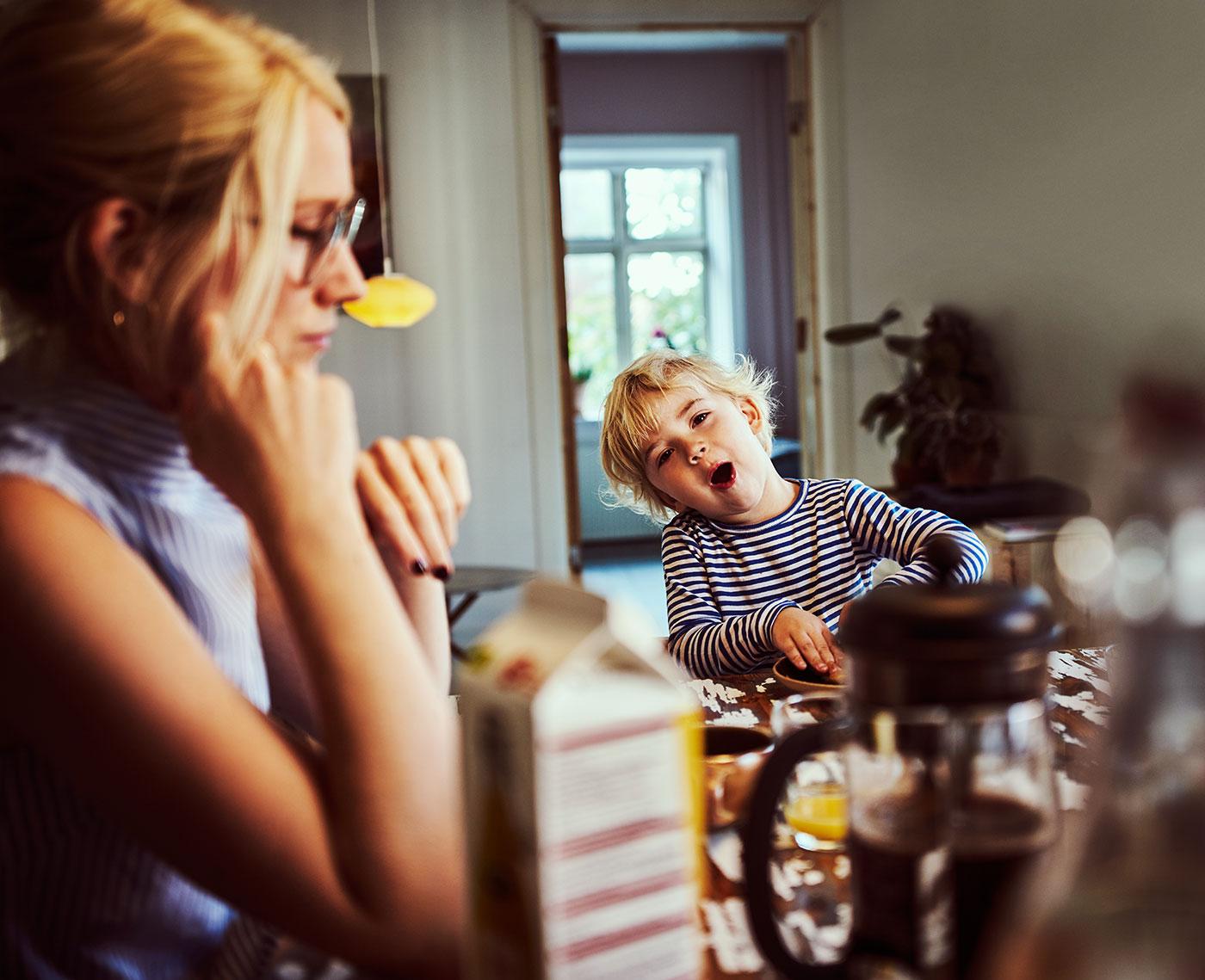 Foto af hverdagssituation ved spisebordet hos en familie. Et barn smiler og fjoller.