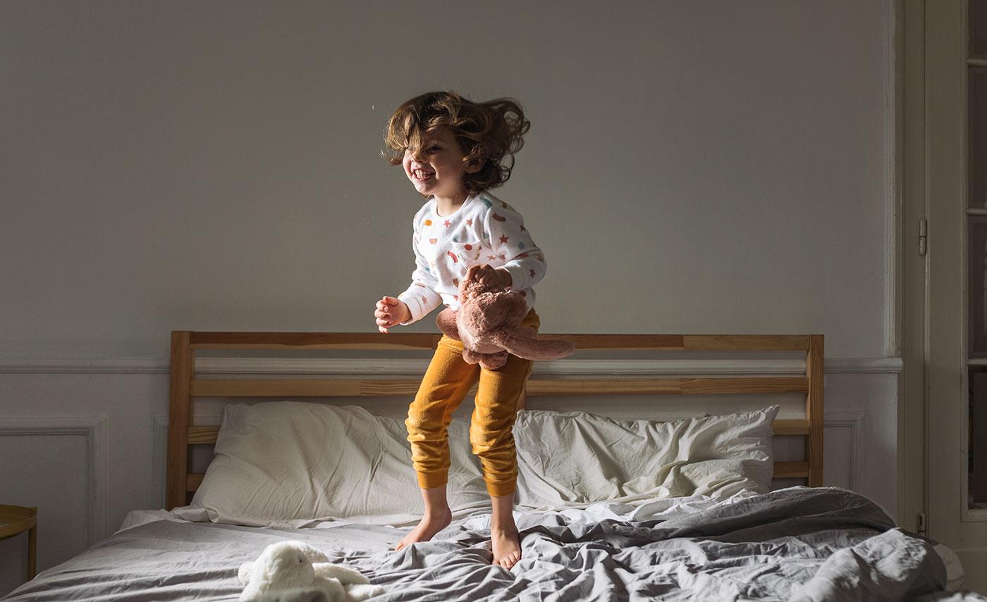 Barn hopper storgrinende i en dobbelt seng