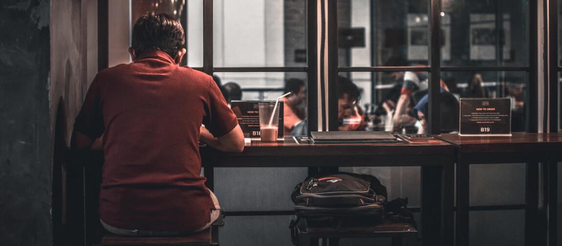 Abbildung eines Mannes, der alleine im Restaurant sitzt.