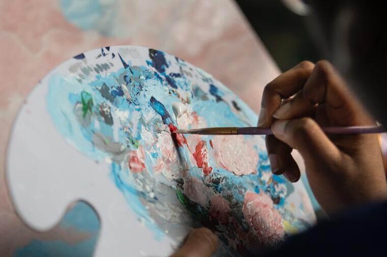 Abbildung einer Hand, die Farben auf einer Mischpalette vermischt