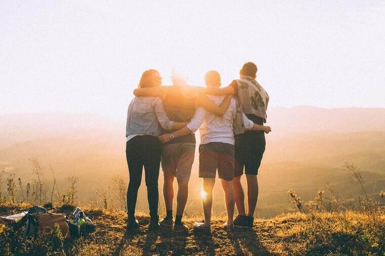 Freundschaftliche Umarmung von vier Personen in der Natur