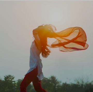 Abbildung einer Frau, die ihre Arme ausstreckt, um ihre Freiheit zu spüren.