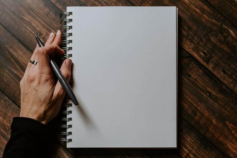 Abbildung eines Notizblocks und einer Hand, die einen Stift hält