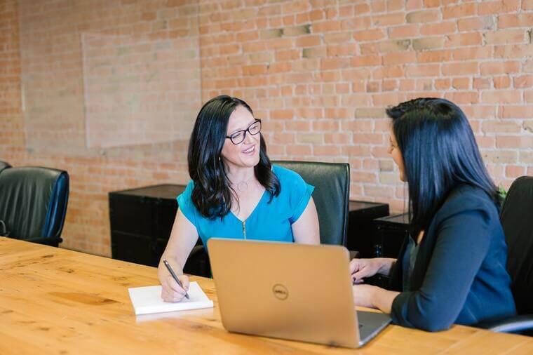 Zwei Frauen, die an einem Tisch sitzen.