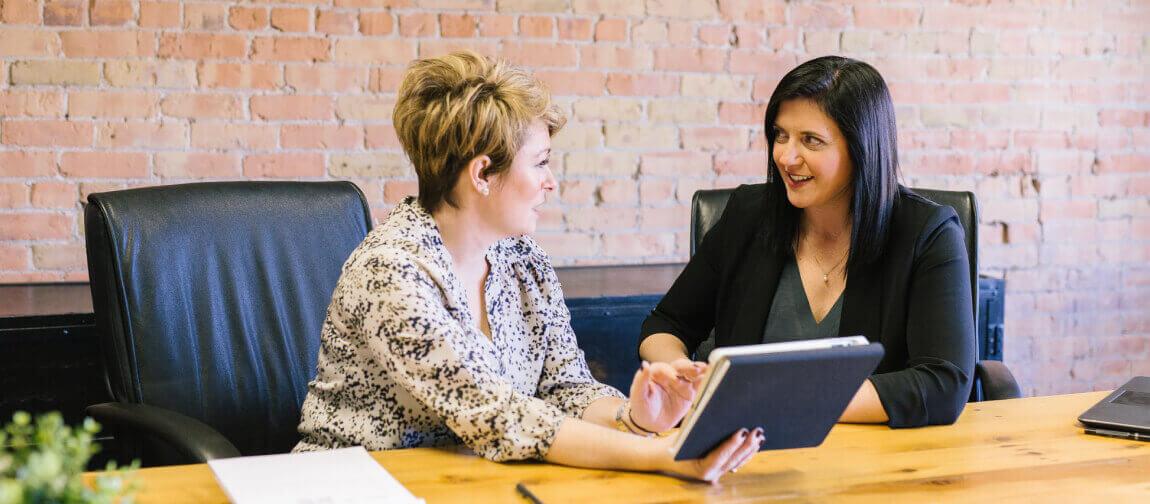 Zwei Frauen, die am Tisch nebeneinander sitzen und sich unterhalten