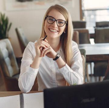 Weibliche Person, die an einem Tisch vor dem Laptop sitzt.