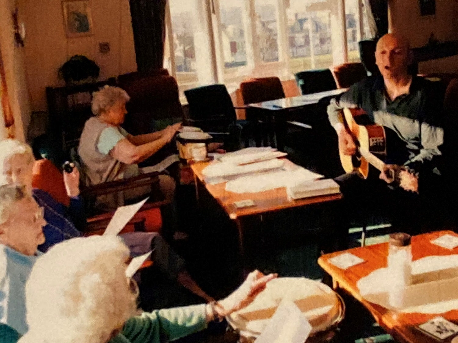 Residents of a care home listening to Steve playing a guitar