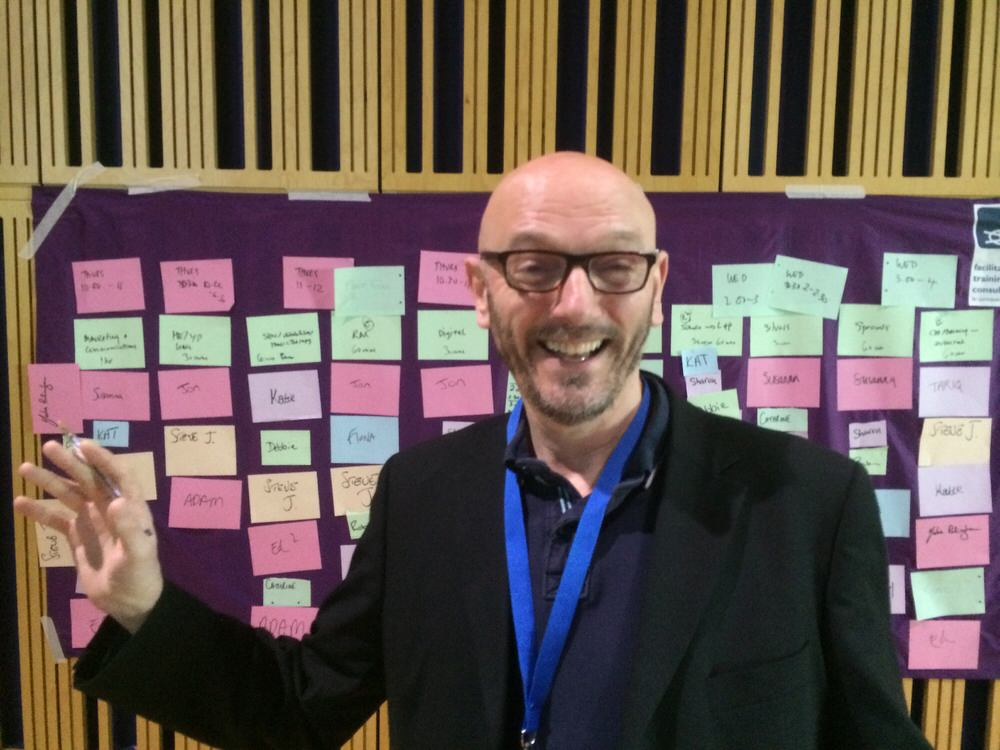 Steve in a business suit smiling in front of a board covered in post it notes.
