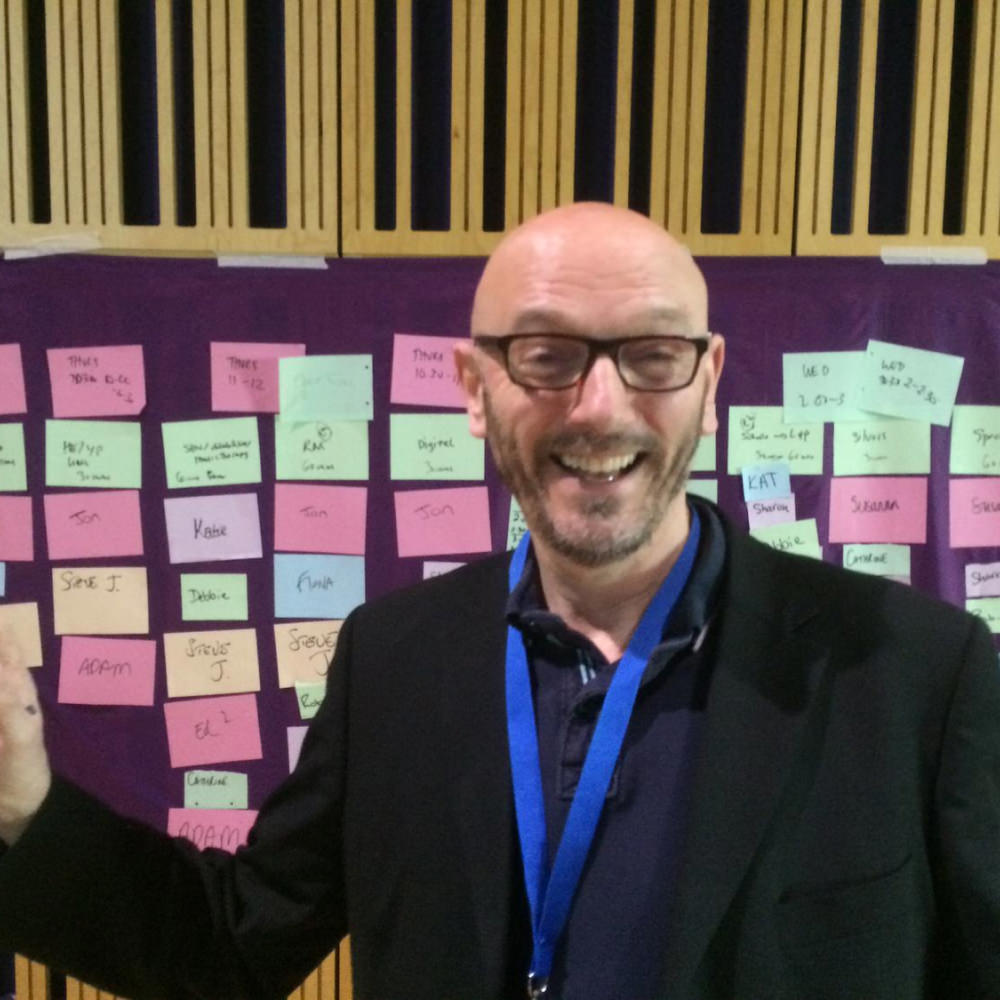 Steve in a business smiling in front of a board covered in post it notes.