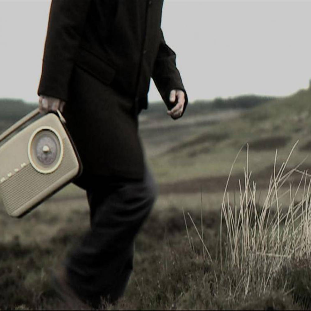 A moody image of Steve carrying a radio over a grass field