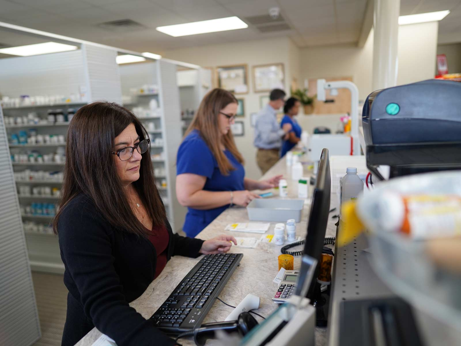 Drive-In Drug Store staff working behind the pharmacy counter