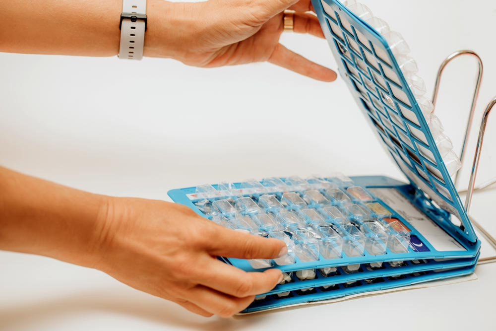 Woman's hand taking pills from blister pack