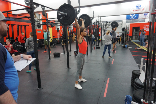 A young girl lifting weight overhead