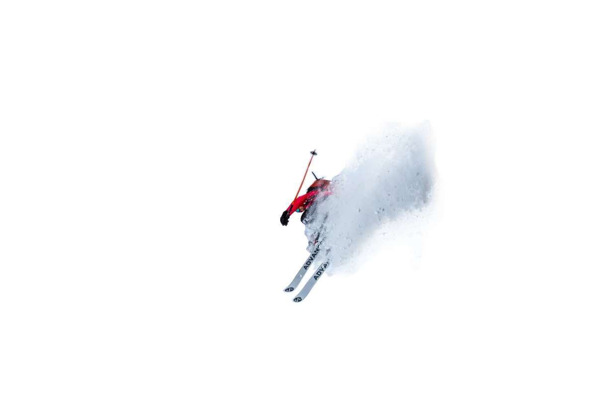 A skier jumping off of the face of a cliff with snow drifting behind them.