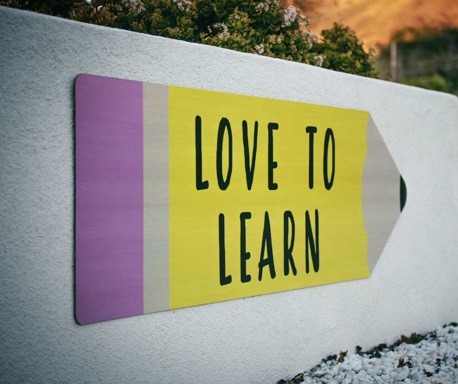 Words Love to learn in colours yellow and purple on a sign shaped like an arrow pointing right