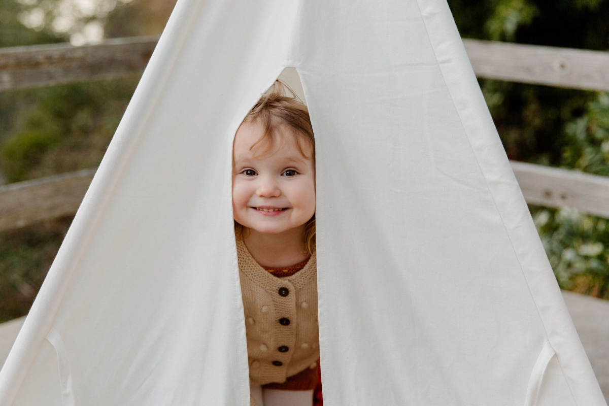 Child aged about three years old, smiling and peeking out from inside a little tent made from white sheets - this is used to represent childhood - by Life Connections Ireland