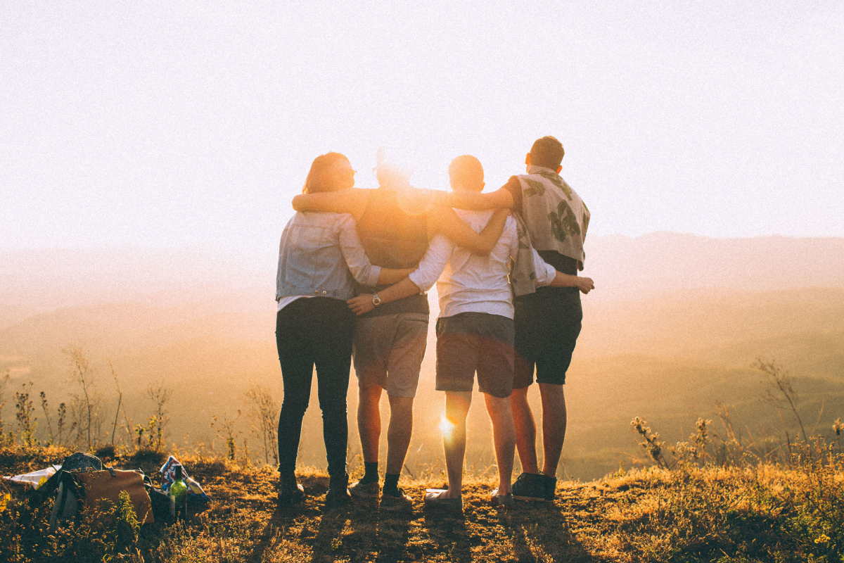 Group of teenage friends with arms around each other, looking into a sunset - chosen to represent healthy boundaries equal healthy relationships by Life Connections Ireland