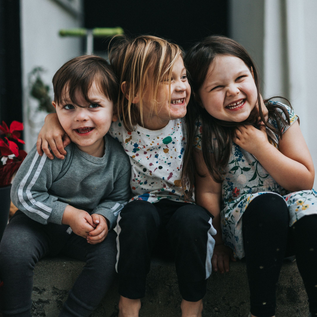 Three children hugging and laughing representing happiness and  curiosity by Life Connections Ireland