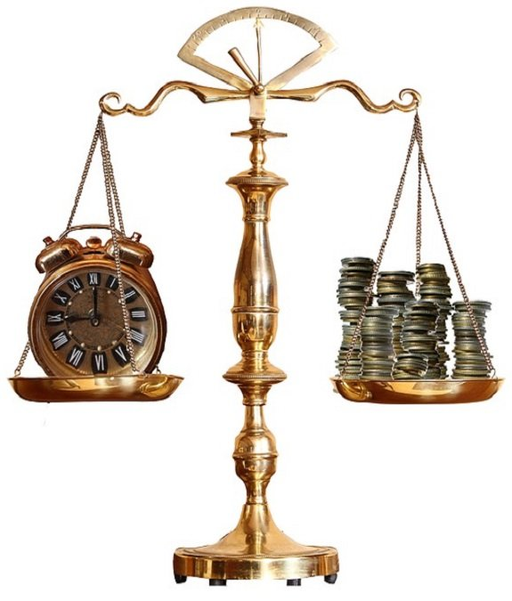 antique brass weighted scale balancing time and money with stacks of coins vs old brass alarm clock.