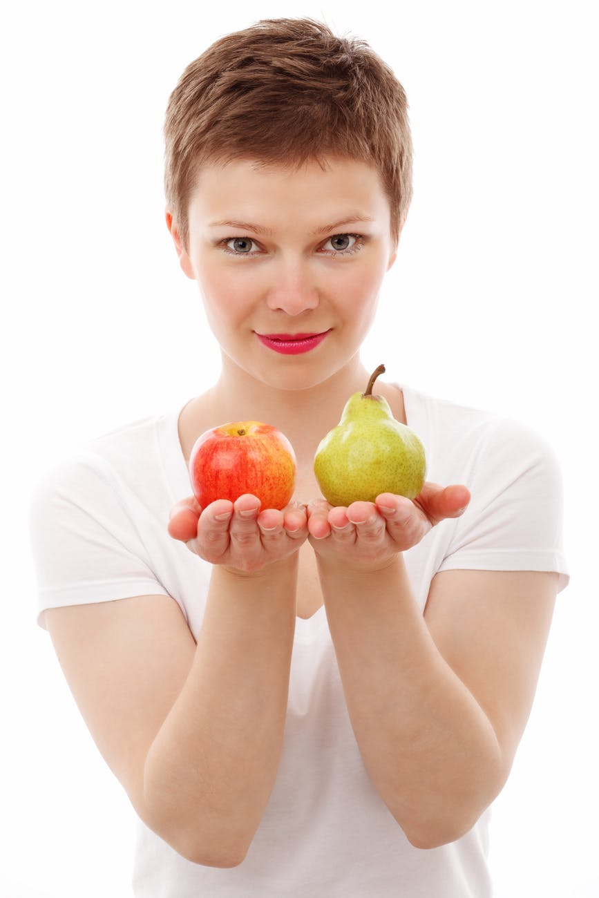 woman holding out two fruits to choose from, an apple or a pear.