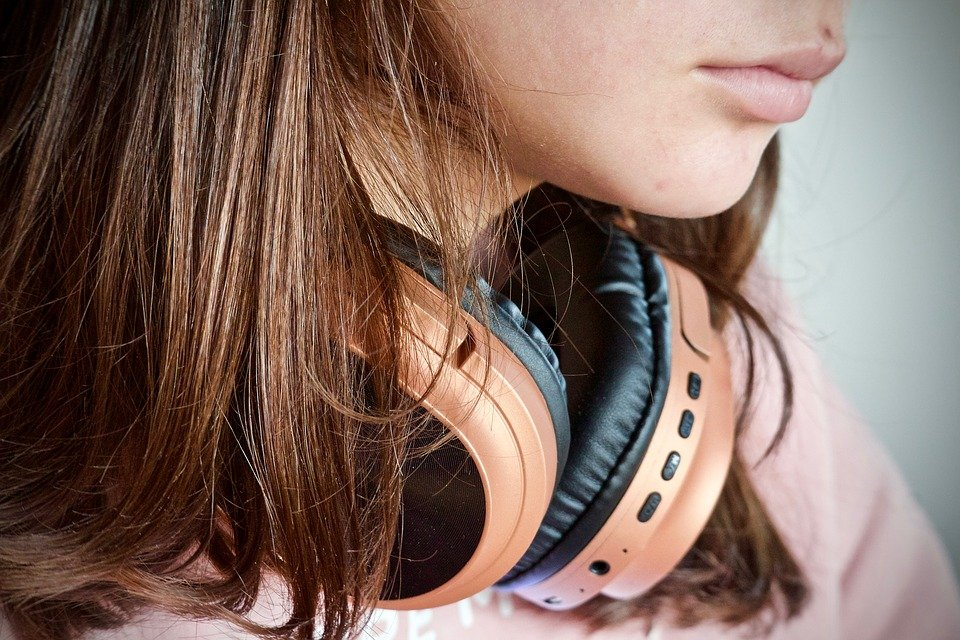 close up photo of teen with long hair and head phones