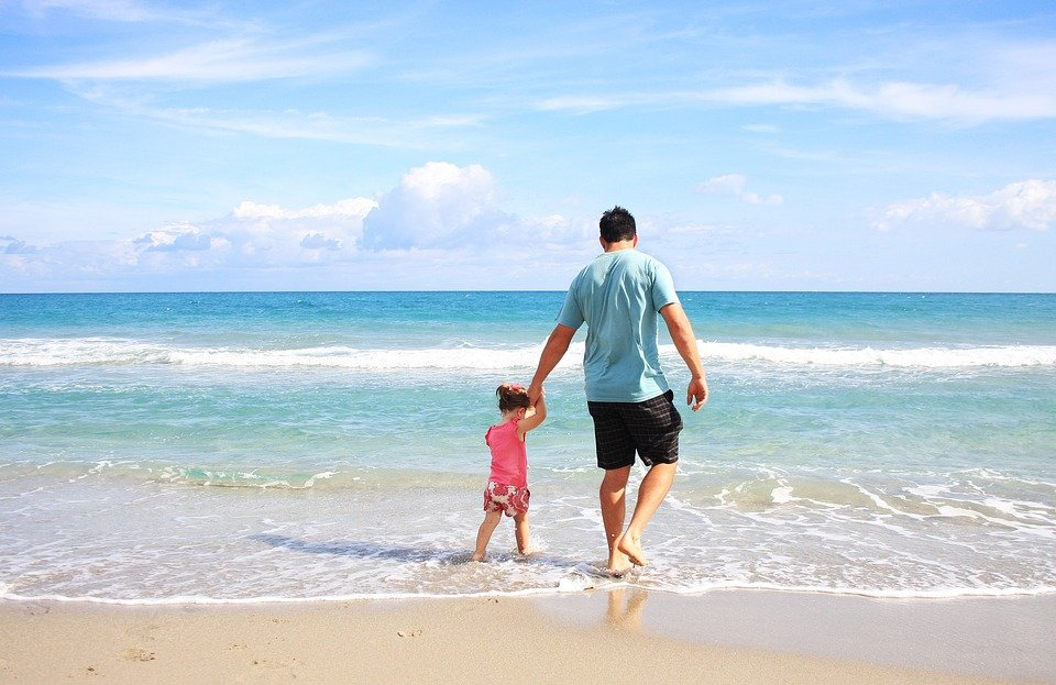 father and daughter wading in gentle tropical beach waves