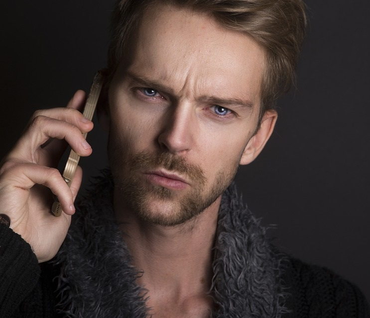 man with concerned look holding smart cellular phone up to his ear