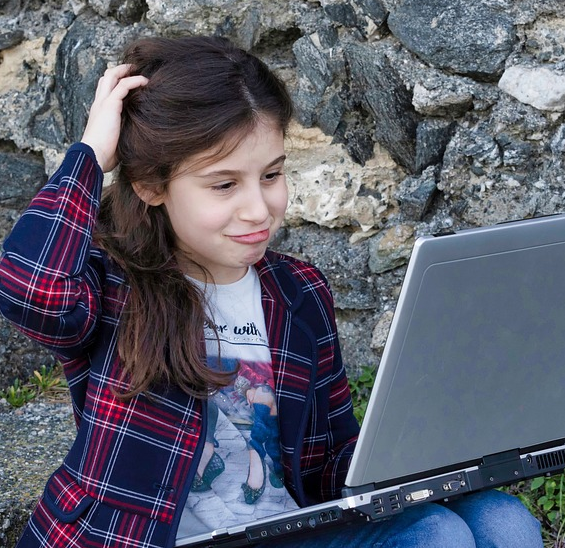 girl scratching her head sitting on rock stairs holding laptop.