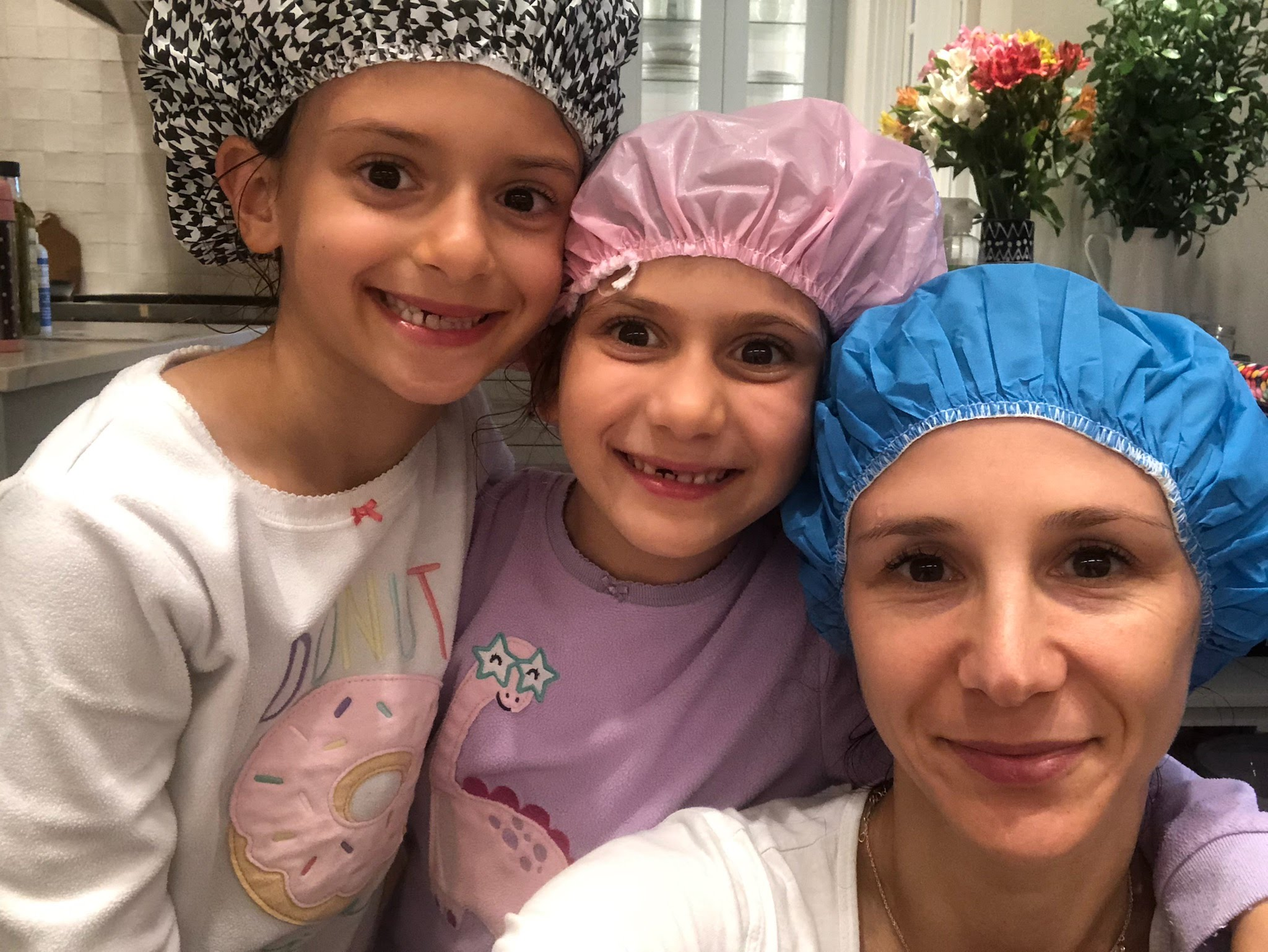 LiceDoctors Technician taking head-to-head selfie with two smiling little girls, all wearing shower caps.