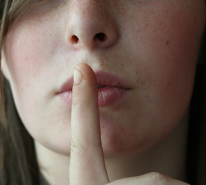 closeup of someone holding finger up to lips suggesting silence SHHH.