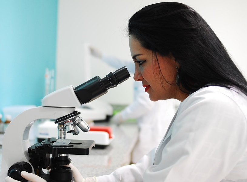 woman with long brown hair and white lab coat looking through microscope.