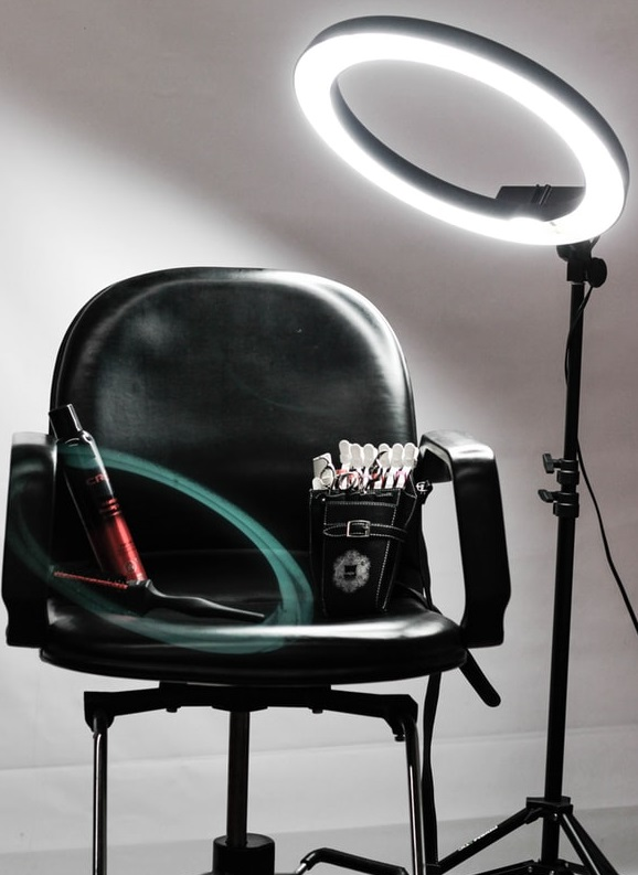 salon chair with bright exam light and hair tools.