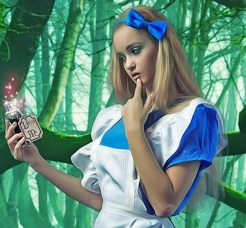 photo of blonde girl dressed like Alice in blue dress with white apron holding DRINK ME potion.