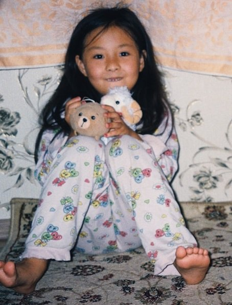 little girl in pajamas sitting in blanket fort under table holding stuffed animals