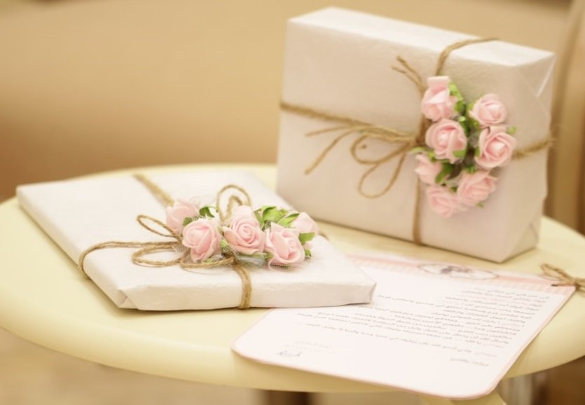 elegant pretty white and pale pink wedding gifts on a table.