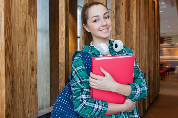 smiling teen girl holding folders and backpack wearing headphones in school hall classroom